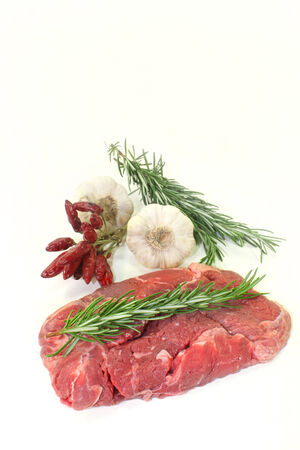 sirloin steak: a piece of raw sirloin steak with rosemary and garlic