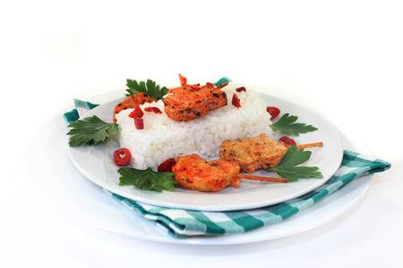 chiles picantes: Pincho con arroz y pimientos calientes en un plato blanco Foto de archivo