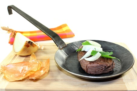 ratite: a piece of ostrich meat in an iron pan
