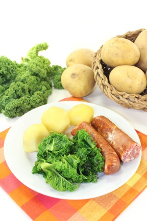 pee pee: a white plate with kale and pee sausage Stock Photo