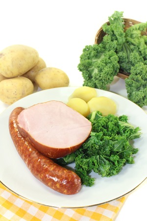 pee pee: a white plate with kale, smoked meat and pee sausage Stock Photo