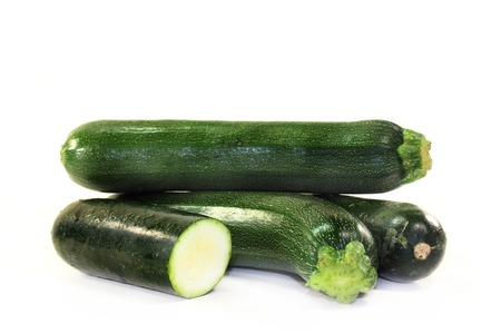 rotund: green, raw zucchini in front of white background