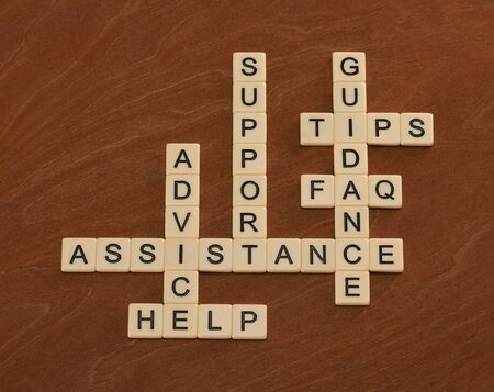 customer support: Crossword puzzle with words Support, Help, FAQ, Assistance. Customer care concept. Ivory tiles with capital letters on mahogany board.