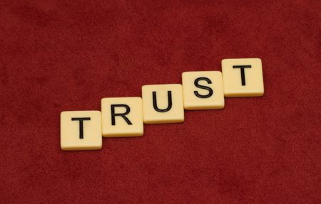 velure: Trust sign. Loyalty concept. Ivory tiles with capital letters on red velure. Stock Photo