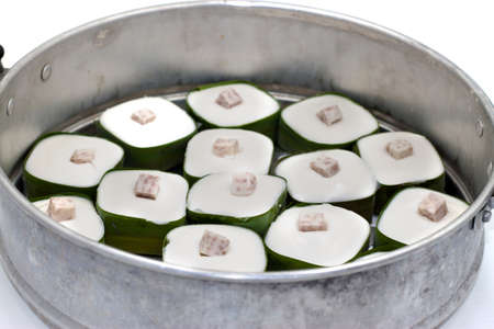 Thai Pudding topping with Taro. Wrapped with banana leaves on aluminum steamer pot. Zdjęcie Seryjne