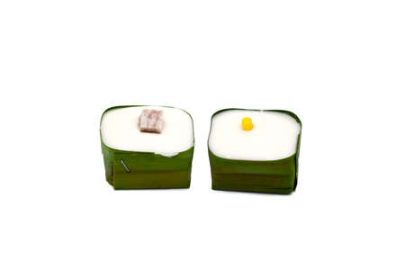 Thai Pudding topping with Taro and Corn. Wrapped with banana leaves. isolated on white background. Clipping path.