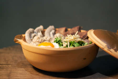Porridge rice or Congee with egg, pork entrails and ginger slide in a clay pot isolated on Dark Slate Gray Concrete Wall background