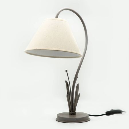 A modern table lamp with a beige lampshade and a metal base, cut out on white background Stock Photo