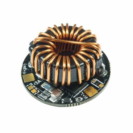 Black round led driver PCB board with inductance coil and surface mount components in a close-up view
