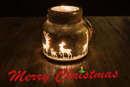 A derivative glowing candle glass in the dark with reindeer on it and the lettering Merry Christmas in the foreground