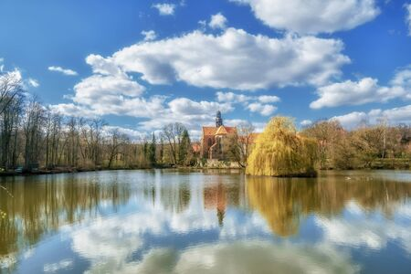 An old monastery in an idyllic atmosphere on a lake in sunshine Stok Fotoğraf - 149543116