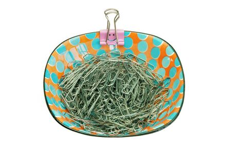 A porcelain bowl with paper clips and a pink smiley paper clip on the edge, white background Stok Fotoğraf