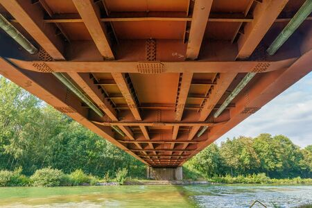 Below a rusty metal railroad bridge under which a river runs