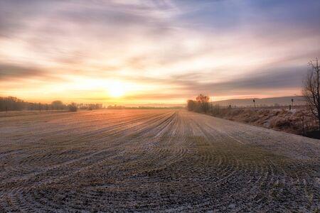 A yellow purple sunrise over a field in winter