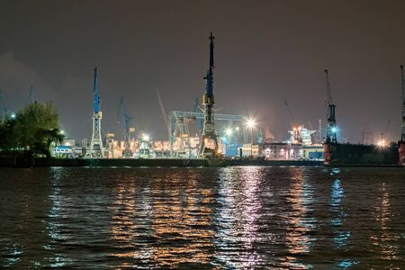An industrial port with cranes at night with colored lights in Hamburg Stok Fotoğraf