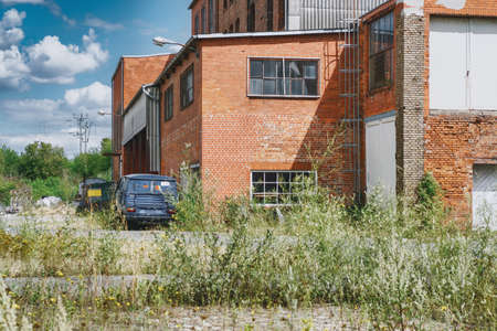 An old abandoned industrial site with a red brick building with a rusty van on it Stok Fotoğraf - 152610505