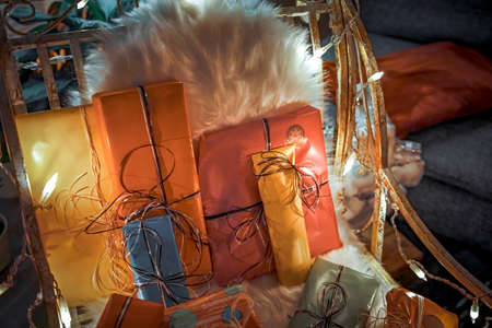 A Christmas lighted chair with gifts and a fur