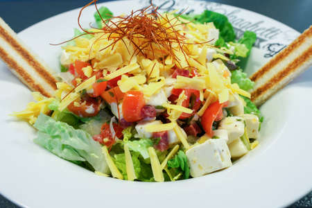 A dish of salad with lots of colorful ingredients, close up