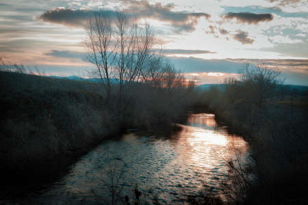 A dreamy sunrise scene by a stream on a December morning