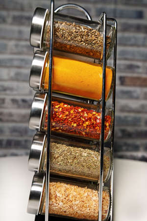 A metal spice rack with many glass bottles filled with different spices, studio shot Stok Fotoğraf