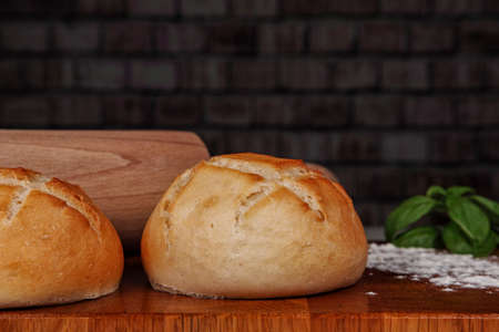 Fresh buns on a wooden board dusted with flour and a rolling pin in the background. Studio shot Stok Fotoğraf