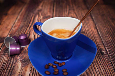 A blue coffee cup with cream coffee stands on a dark brown wooden surface. Coffee beans are next to it Stok Fotoğraf