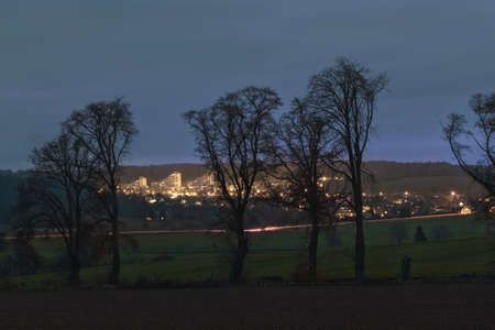 A small illuminated town behind the fields in the dark