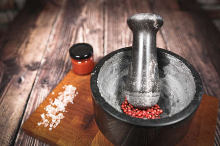 Kitchen mortar with red berries on a wooden board