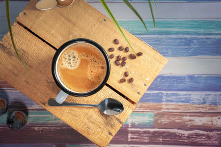 A white coffee cup with cream coffee stands on a colored wooden wooden surface. Coffee beans are next to it