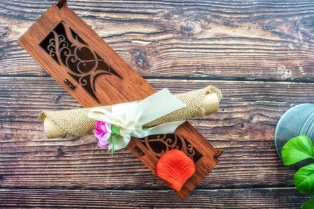An ornate wooden box with parchment wrapped in fabric and flowers Stok Fotoğraf