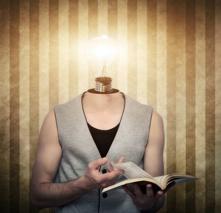 Young male reading a book with a light bulb  instead of head photo