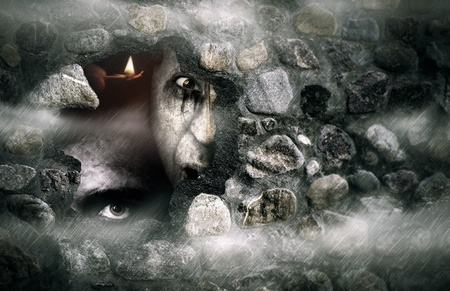 Halloween concept  of a broken stone wall with zombies photo