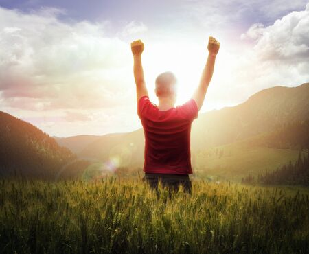 Young man with arms raised looking at sunset with mountains ahead Stock Photo - 10569919