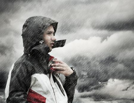 lloviendo: Joven sentado bajo la lluvia