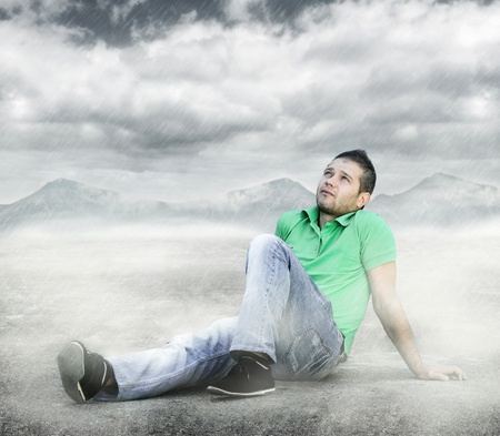 hoping: Young man sitting on the ground and looking to the sky Stock Photo