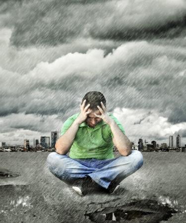 la société: Jeune homme qui est assis sur l'asphalte et de la pensée Banque d'images