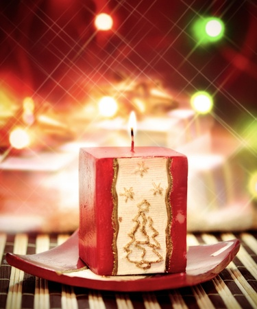 Christmass candle with gifts and lights photo
