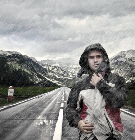 lloviendo: Hombre joven caminando en la calle desierta, mientras que está lloviendo