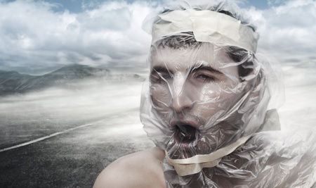 Young man in the desert with a bag on his head trying to breathe photo