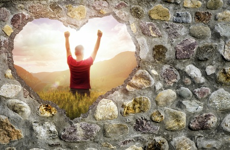 Broken stone wall in a shape of heart and a young man raising his hands up photo