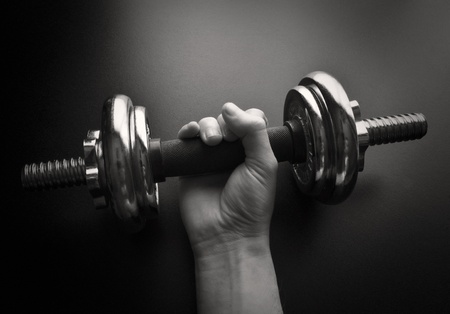 free time: Young man working out with a  dumbbell-NOTE:Grain and contrast was added Stock Photo