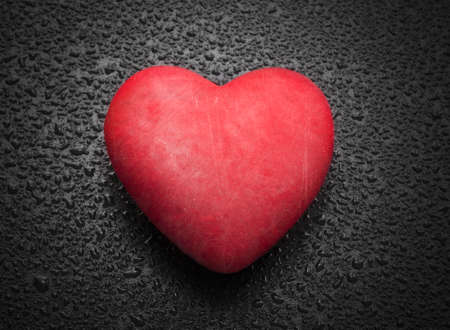 Red heart on wooden background with raindrops photo