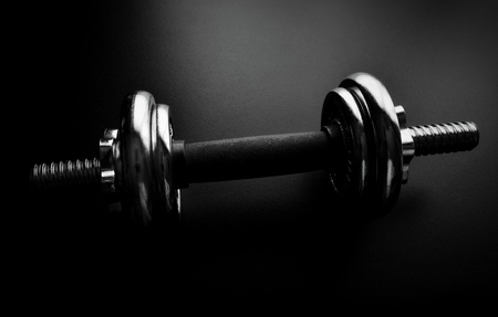 Close-up of an chrome dumbbell on dark background