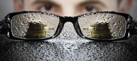 Young businessman looking at glasses