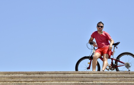 Young man on bicycle against a blue sky