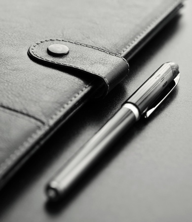 Close-up of a black personal agenda and with a pen with selective focus photo