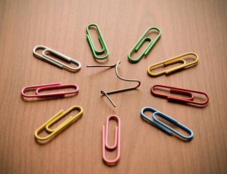 broken unity: Paper clips on wood background illustrating a unique concept