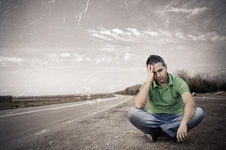 Oude foto van een jonge man zitten uit de weg: NB-Textuur werd toegevoegd aan een oude afbeelding te simuleren.