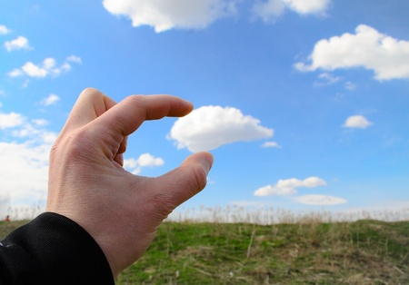 Human hand reaching for a cloud and grabing it photo