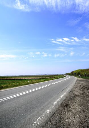 Horizontal image of a country road with blue sky in the summer photo